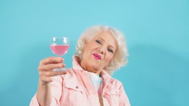 glückliche positive Oma mit Glas, die in die Kamera schaut und ihren Geburtstag feiert. Glück, positive Emotionen und Gefühle.