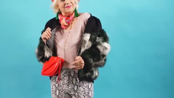Lächelnd tanzt eine ältere Dame und blickt in die Kamera. isolierter gelber Hintergrund.