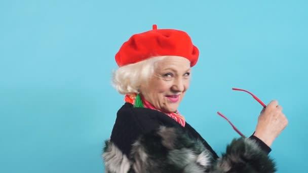lachende fröhliche Oma in roter Mütze und schwarzem Mantel