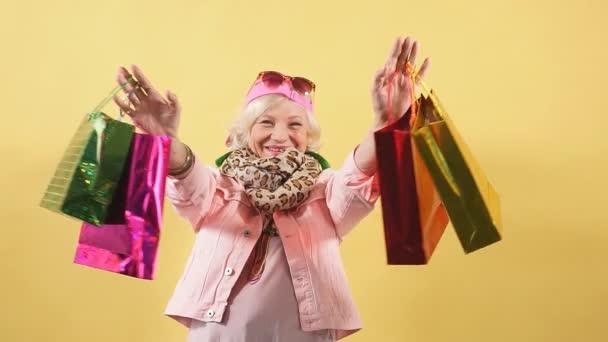 fröhliche coole Oma mit erhobenen Armen, die viele Einkaufstüten in der Hand hält