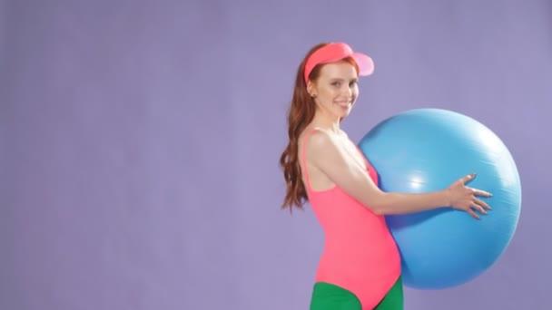 sportliches süßes Ingwergirl macht Übungen mit blauem Fitnessball, macht Aufwärmtraining