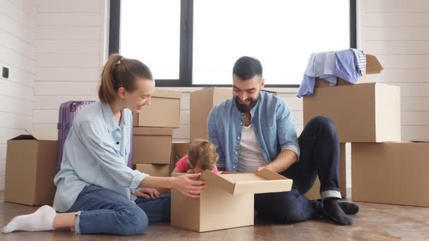 junge Familie sitzt auf dem Boden, umgeben von Kisten.