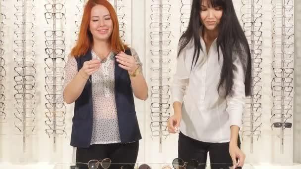 dvě skvělé dívky snaže se o sluneční brýle, okno s různými modely brýlí na pozadí.