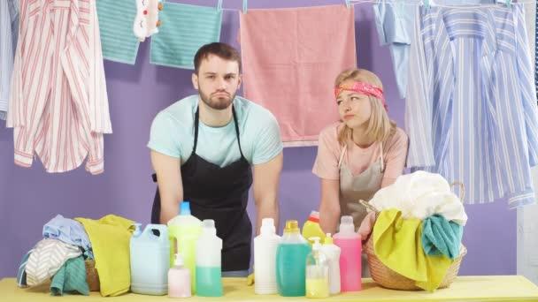 nette junge Familie ist dabei, Wäsche zu waschen.