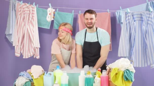 verrückter Mann und Frau weinen aus Verzweiflung, fühlt sich nach dem Waschen von Kleidung überlastet