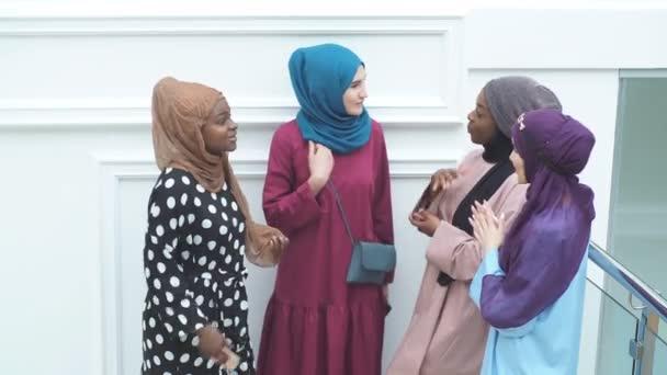 Gruppe multiethnischer muslimischer Geschäftsfrauen in modischen traditionellen Kleidern, die mittags miteinander reden