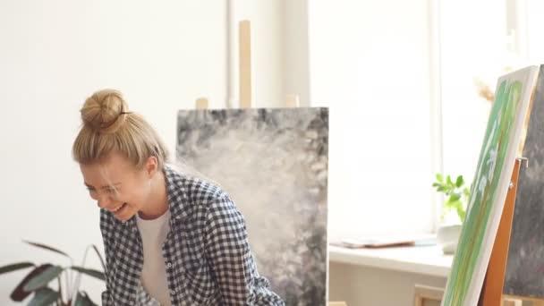 Szőke lány dolgozik spatula a művészeti stúdió
