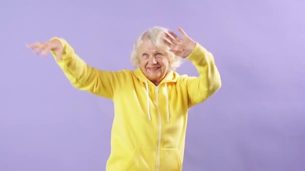 stylische Oma im gelben Sport-Sweatshirt, die sich zu Musik, Tanzparty, Stil bewegt.