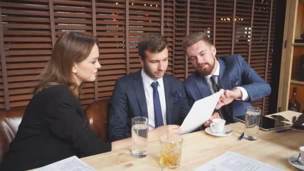 Mladí podnikatelé diskutují o podmínkách smlouvy na obchodní schůzce