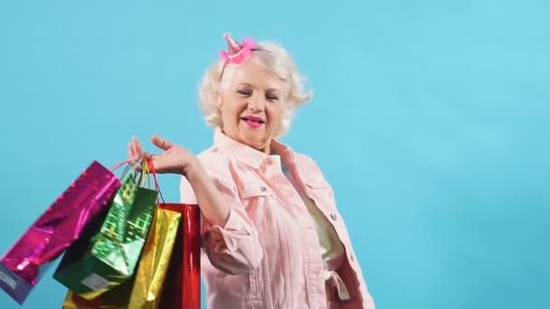 Mosolygó pozitív nagyi bevásárló táskák mutatják hüvelykujj fel.