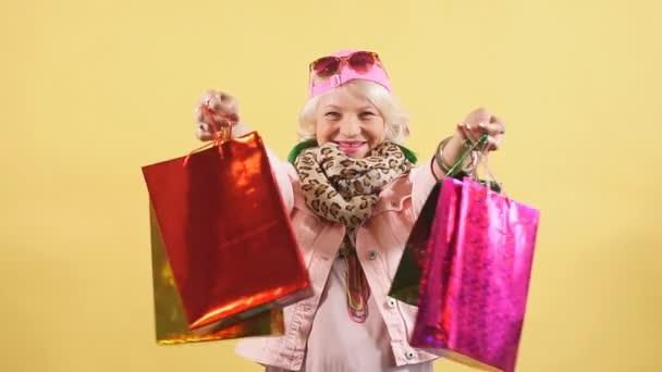 hübsche Oma hat Geschenke, Kleidung für ihre Enkelinnen und Enkel gekauft.