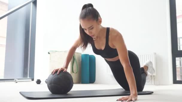 Beautiful female athlete performs push ups on fitness ball