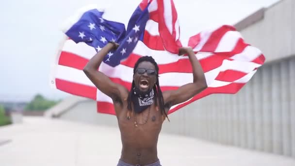 African American male protester waves an American flag in the street