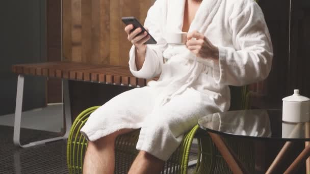 Mladý muž relaxuje v lázních, pije čaj a spí online s přáteli