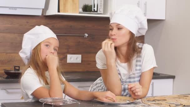 Roztomilá dcera se svou matkou v zástěrách a klobouky kuchaři tráví čas v kuchyni se chystá vařit lahodný dort