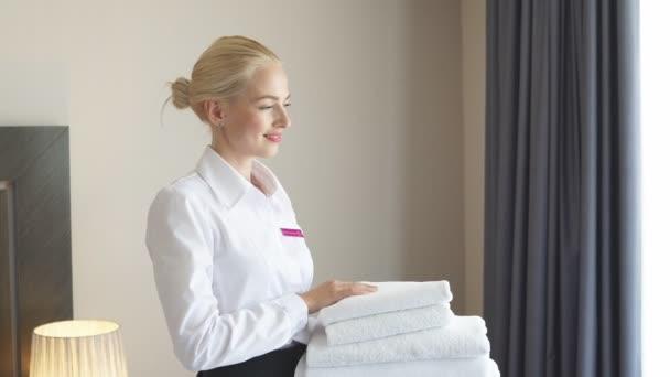 Atraktivní pokojská s ručníky v rukou