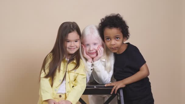 Three diverse children with unusual appearance hug each other, posing