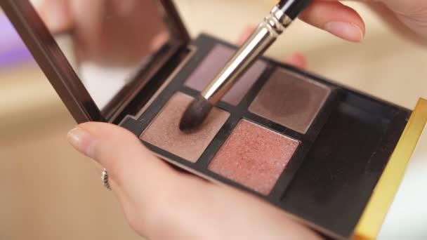 Make-up umělec použít štětec a dekorativní kosmetiku při výrobě make-upu