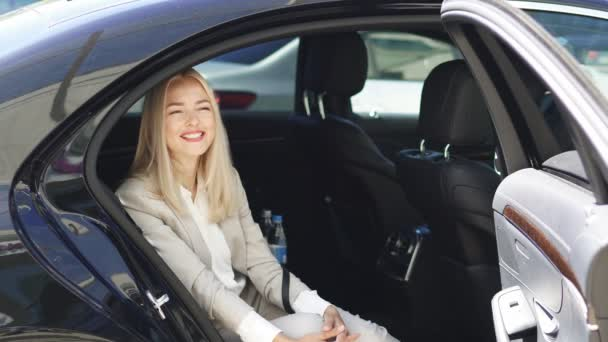Attractive business lady sitting inside of luxurious car