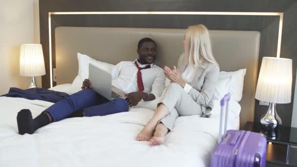 Schönes Paar liegt mit Laptop im Bett