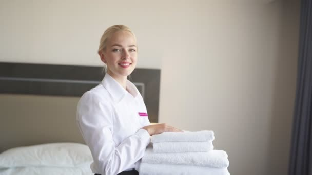 Good-looking chambermaid with white linen and towels in her hands