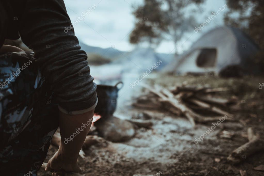 Camp and cooking in field conditions, boiling pot at the campfire on picnic in morning. Cooking dinner on firewood stove using firewood when going to the wilderness or outdoor activity, camping tent
