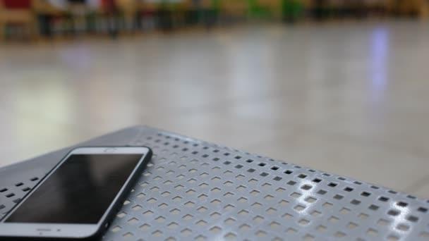 Elfelejtett smartphone vagy mozgatható telefon, egy padon. Jogdíj kiváló minőségű ingyenes stock videofelvétel valaki elhagyja egy pad, ahol elveszett sejt telefon-val fekete képernyő padon nyilvános terület