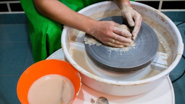 A raw clay pot in the hands of a potter. Workshop in the pottery workshop