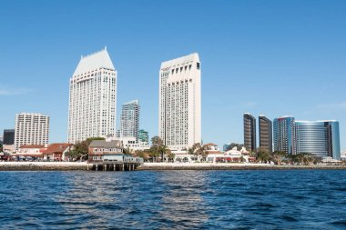 SAN DIEGO, CALIFORNIA - MARCH 2, 2017:  Seaport Village shopping and dining complex with the downtown skyline, including waterfront hotels.