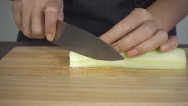 Zeitlupe - Großaufnahme der Chefin, die Salat gesund macht und Gurken auf Schneidebrett in der Küche schneidet.