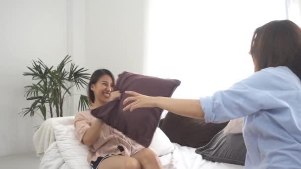 Zeitlupe - Asiatische junge lesbische Paar spielen einander mit Liebesmoment auf dem Sofa im Schlafzimmer umgeben von warmem Sonnenlicht. Lgbt-Paar haben einen Liebesmoment zusammen auf dem Sofa zu Hause.