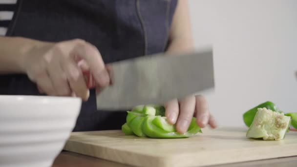 Close up of chief woman making salad healthy food and chopping bell pepper on cutting board.