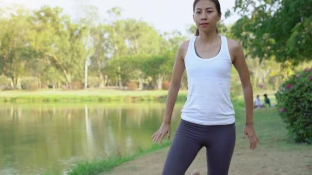 Junge asiatische Frau Yoga im Freien bleiben Sie ruhig und meditiert beim Üben von Yoga, die innere Ruhe zu erkunden. Yoga und Meditation haben gute Vorteile für die Gesundheit. Yoga-Sport und gesunde Lifestyle-Konzept.