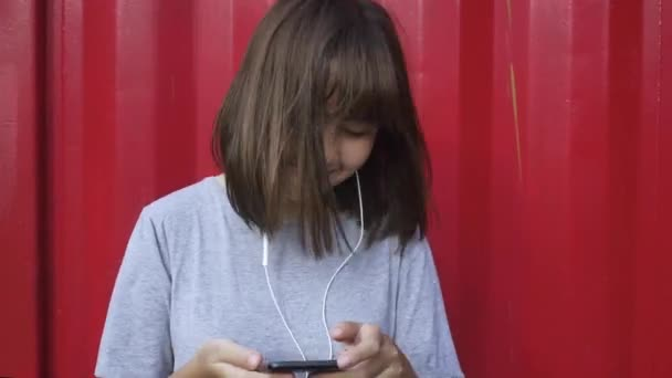 Beautiful young asian woman listening to music on a smart phone in the city. Young asian woman relaxing listening to music on the street.