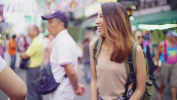 Slow motion - Traveler backpacker asian woman travel in Khao San road at Bangkok, Thailand. Happy young female spending holiday trip at amazing landmark and enjoy her journey in traditional city.