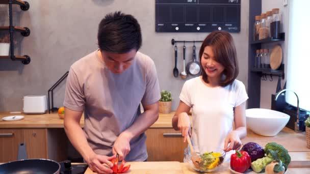 Člověk ruce řezání rajče v kuchyni. Krásné asijské šťastný pár se vaření v kuchyni. Mladý asijský pár mají romantický čas při pobytu doma. Životní styl několik domácí koncept.