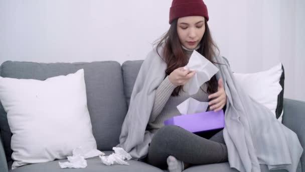 Die kranke junge Asiatin hat Kopfschmerzen, wenn sie zu Hause auf einem Stuhl sitzt, der in eine graue Decke gehüllt ist. schöne Weibchen im Winter und Weihnachtsfest pusten die Nase und verwenden Gewebe.
