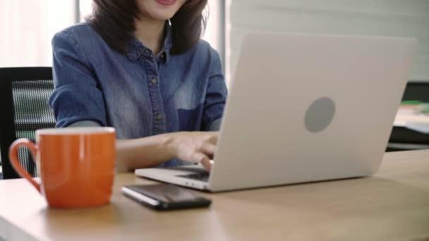 Krásná mladá usměvavá Asijské žena pracující na notebooku zároveň pomocí smartphone v kanceláři. Asijské obchodní žena pracovní dokument financí v domácí kanceláři. Těší se na čas v kanceláři.
