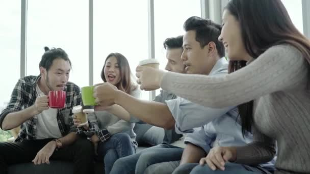 Eine Gruppe junger Leute hält Kaffeetassen in der Hand und diskutiert lächelnd etwas, während sie auf der Couch im Büro sitzen. Kaffeepause im Kreativbüro.
