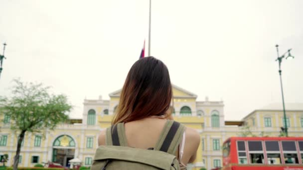 Slow motion - Traveler backpacker asian woman travel in Bangkok, Thailand. Happy young female spending holiday trip at amazing landmark and enjoy her journey in traditional city.