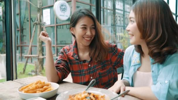 schöne glückliche asiatische Frauen lesbisch lgbt Paar sitzt auf jeder Seite essen einen Teller mit italienischen Meeresfrüchten Spaghetti und Pommes im Restaurant oder Café, während lächelnd und Blick auf Essen.