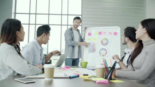 Skupina lidí neformálně oblečený obchodní diskusi o myšlenky v kanceláři. Kreativní profesionály, kteří se sešli na zasedání stolu pro diskutovat o důležitých otázkách nové úspěšné spuštění projektu.