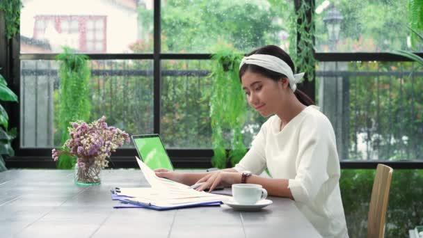 schöne junge lächelnde asiatische Frau, die am Laptop arbeitet, während sie zu Hause im Wohnzimmer sitzt. asiatische Geschäftsfrau arbeitet Dokumentenfinanzierung und Rechner in ihrem Homeoffice. Zeit zu Hause genießen.