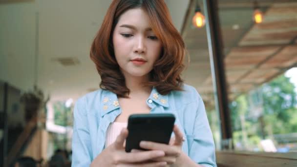 Veselý šťastný asijské mladá žena sedí v kavárně pomocí smartphone pro mluvení, čtení a posílání SMS zpráv. Koncept ženy životní styl.