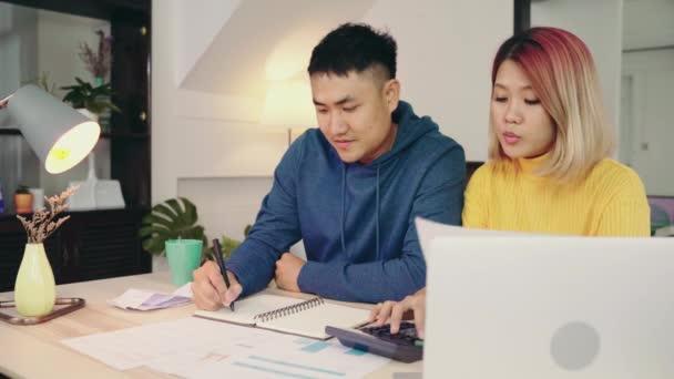 Mladý asijský pár Správa financí, kontrola jejich bankovní účty pomocí přenosného počítače a Kalkulačka v moderní domov. Žena a muž dělá papíry pohromadě, platící daně online na notebooku