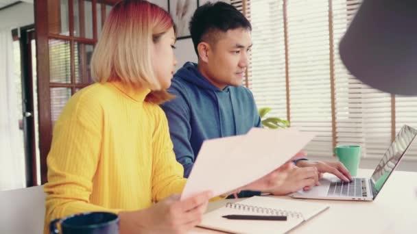 Mladí zdůraznil asijský pár, Správa financí, kontrola jejich bankovní účty pomocí přenosného počítače a Kalkulačka v moderní domov. Žena a muž dělá papíry pohromadě, platící daně online