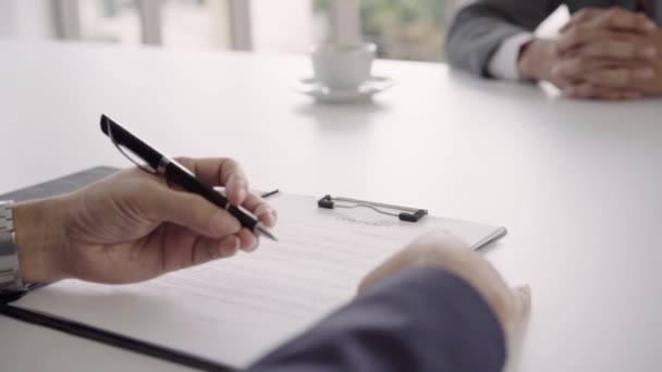 Slow motion - Smart handsome businessmen meeting in workplace with his colleague and signing a contract, recruitment and agreement concept. Male making a deal.