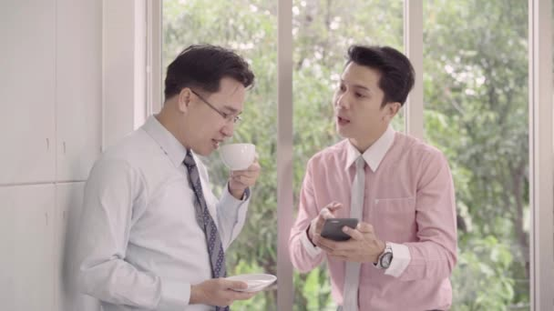 Slow motion - Young smiling men enjoying drinking warm coffee standing while relax in office. Asian business man using smartphone. Male talking together in relax time.