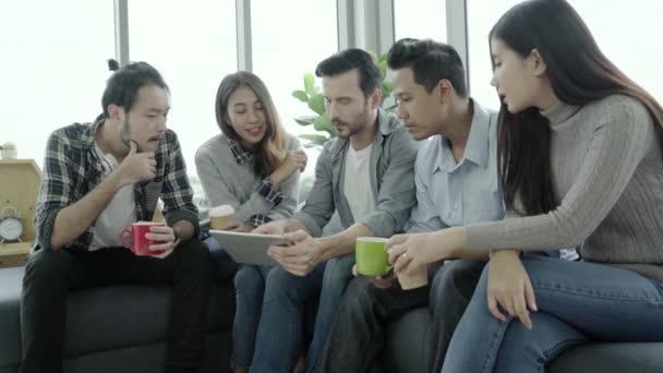 Multiethnische Kreativteam Vielfalt der Jugendlichen Gruppenteam holding Kaffeetassen und Ideen Treffen mit Tablet auf der Couch im Büro sitzen zu diskutieren. Kaffee-Pause-Zeit in kreative Büro