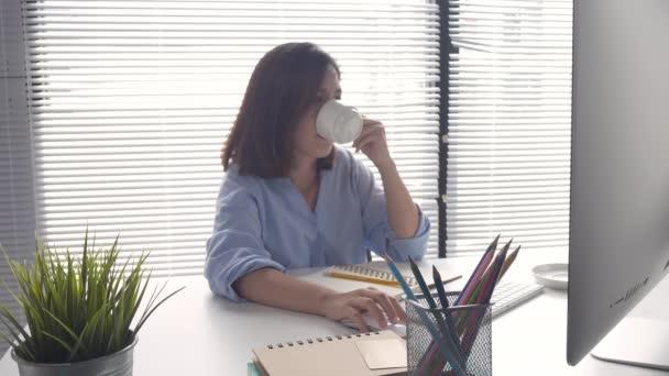 Gyönyörű fiatal mosolygó ázsiai nő számítógépen dolgozik, és kávét iszik otthon a nappaliban. Asia üzletasszony pénzügyi dokumentum és az ő otthoni irodai számológép.